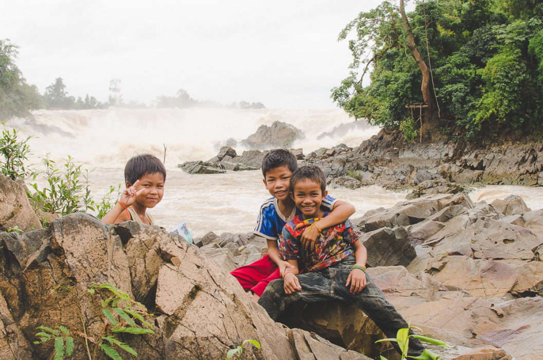 Kids posing in front of the camera and waterfall behind in Laos taken by Milie Del