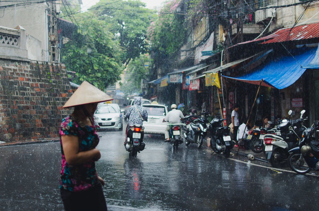 girl running under the rain in Hanoi Vietnam taken by Milie Del