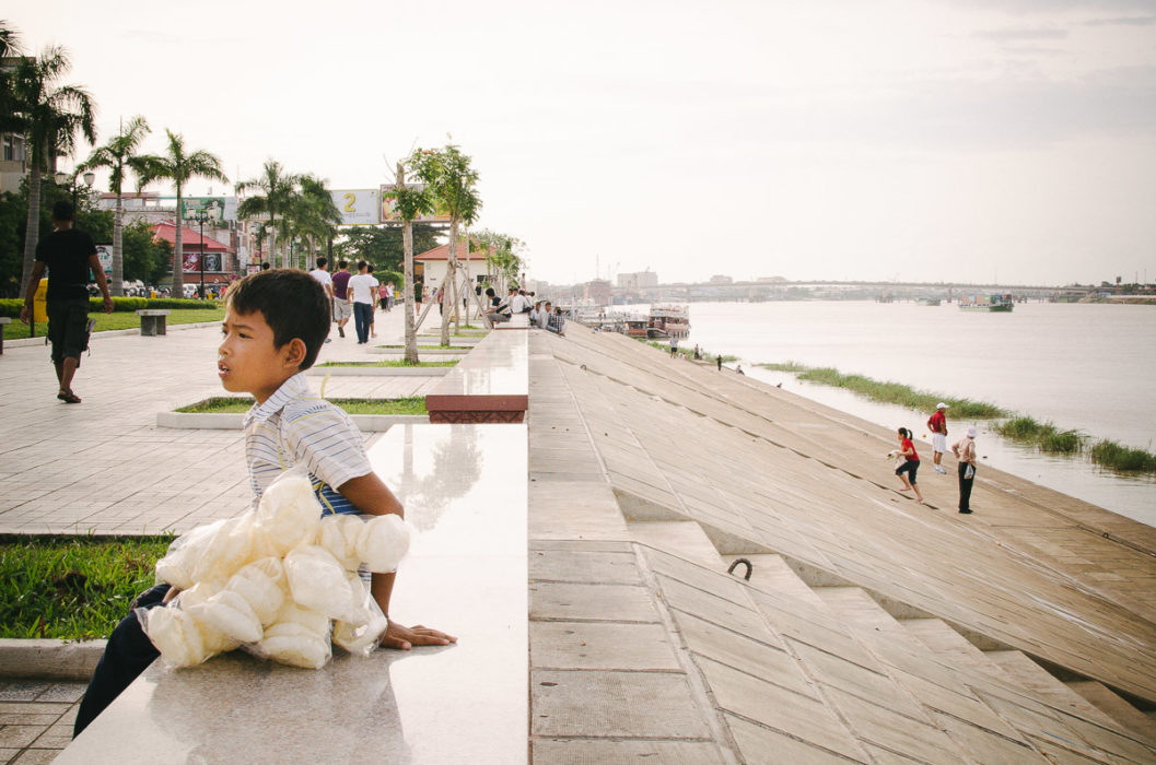 Boy sitting near mekong river in Phnom Penh in Cambodia taken by Milie Del