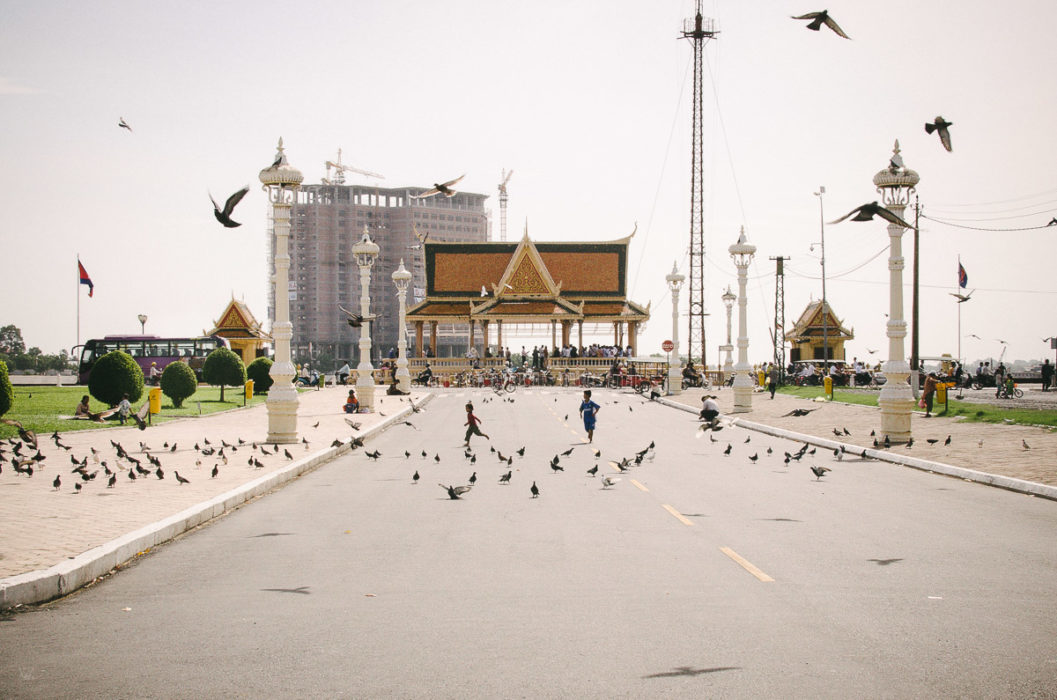 little boys running after pigeons in Phnom Penh in Cambodia taken by Milie Del
