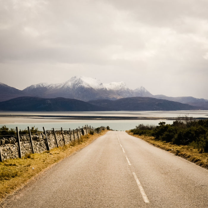 Beautiful country Road with snow capped peaks near Tongue Scotland taken by Milie Del