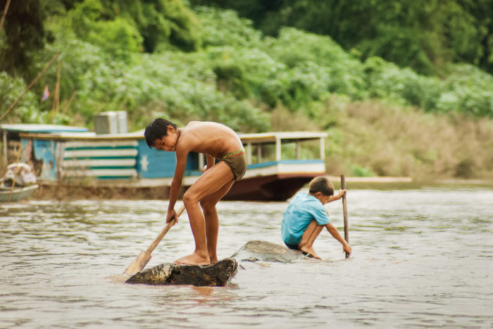 two Kids on a branch paddling in the mekong river in Laos taken by Milie Del