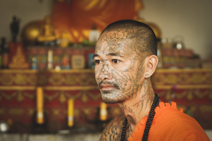 portrait of a tatoued Monk in orange outfit Laos taken by Milie Del