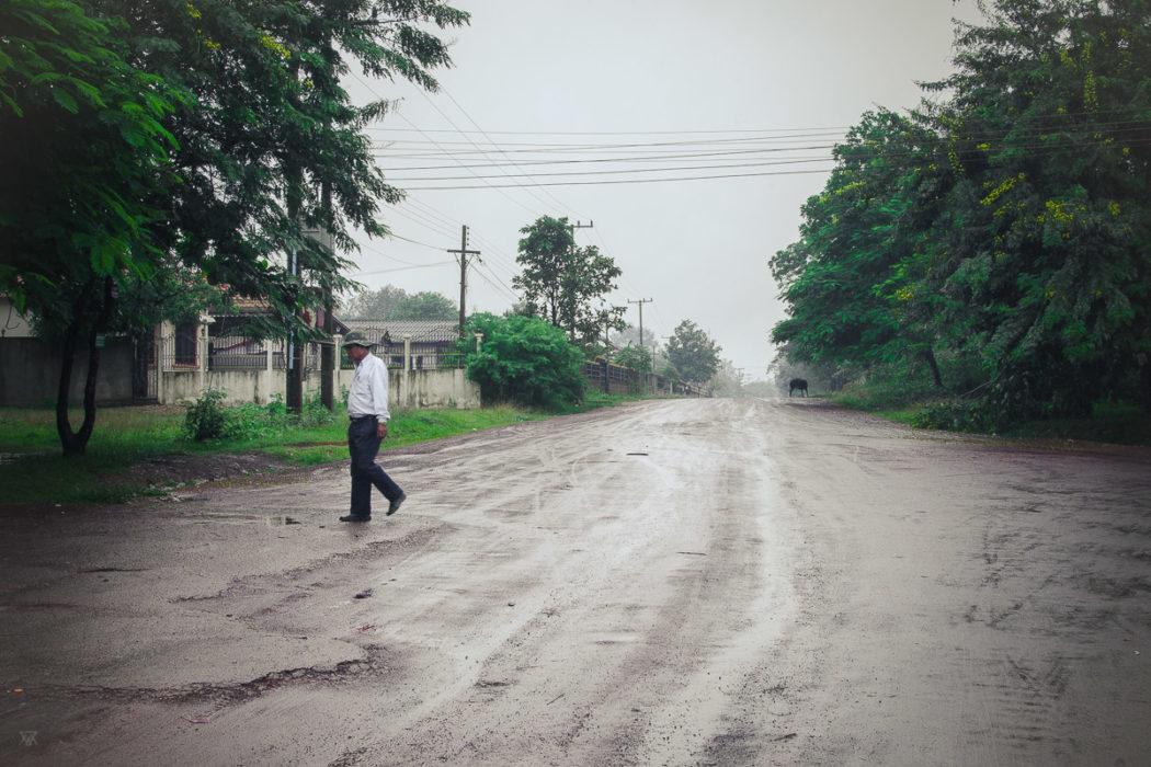 Man crossing the road near the salt factory under the rain near Vientiane Laos taken by Milie Del