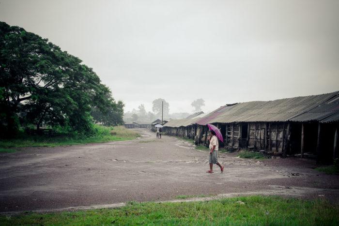 Man crossing the road near the salt factory under the rain near Vientiane Laos taken by Milie Del