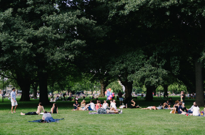 People sitting down in the grass at the park, London taken by Milie Del
