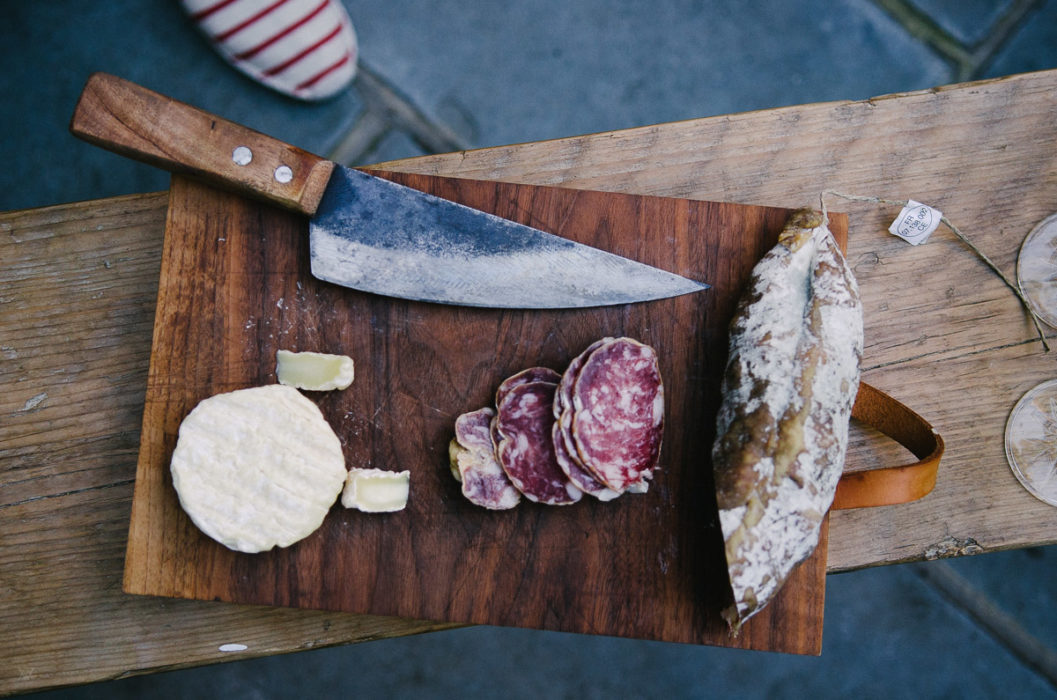 French aperitif with saucisson and cheese set on wooden table - London