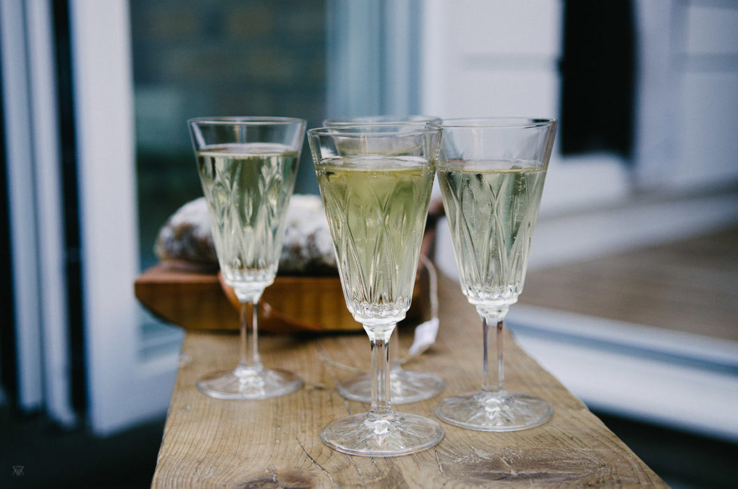 glasses of champagne set on wooden table - London