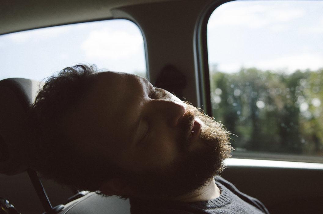 Man asleep in a car, Tuscany, Italy