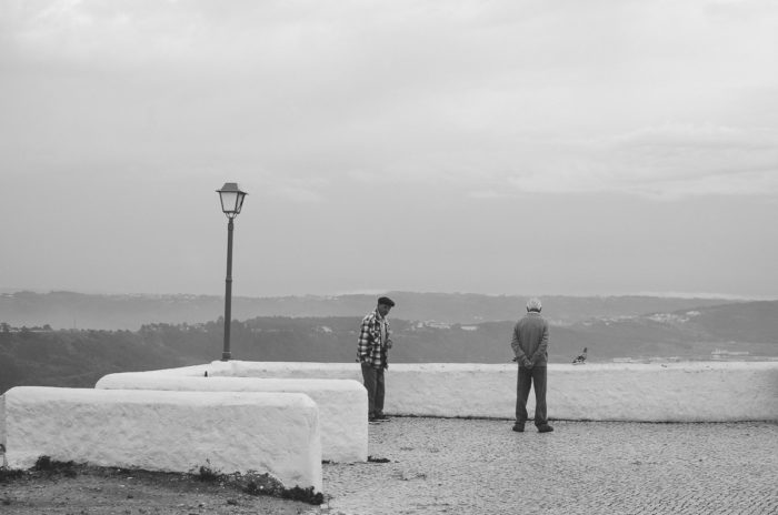 black and white picture of 2 old men meeting in Nazare old town Portugal
