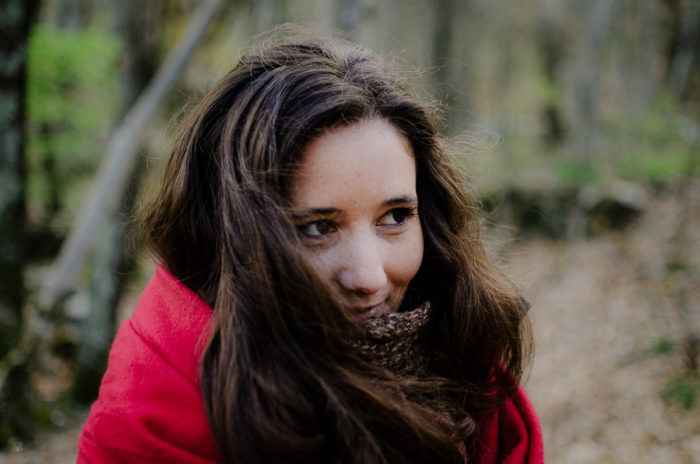Portrait of a girl in red in a forest taken by Milie Del