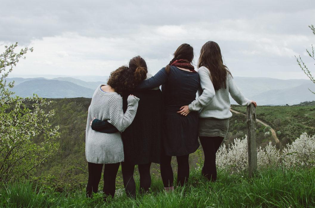 Four girls hugging and watching horizon