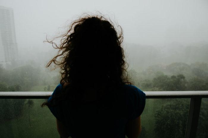 cheveux vent femme regardant pluie tropical immeuble