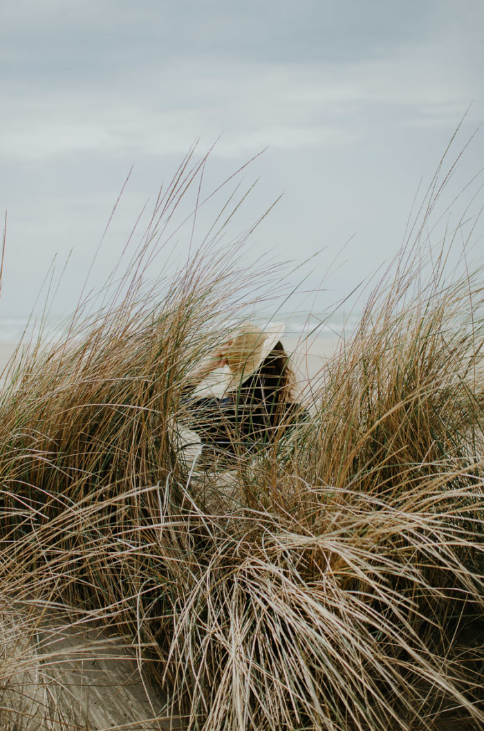 girl holding a straw hat in the dunes at the beach of Piemanson