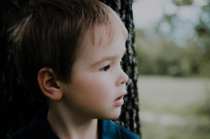 portrait petit garçon adossé tronc arbre