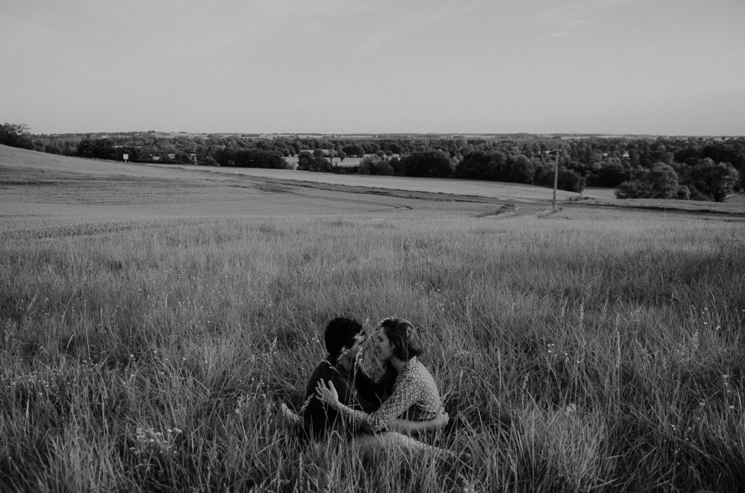 Photographie noir blanc couple assis herbe session lifestyle