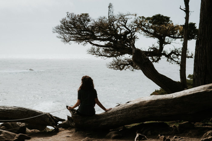 Girl sitting branch facing pacific ocean Big sur coast