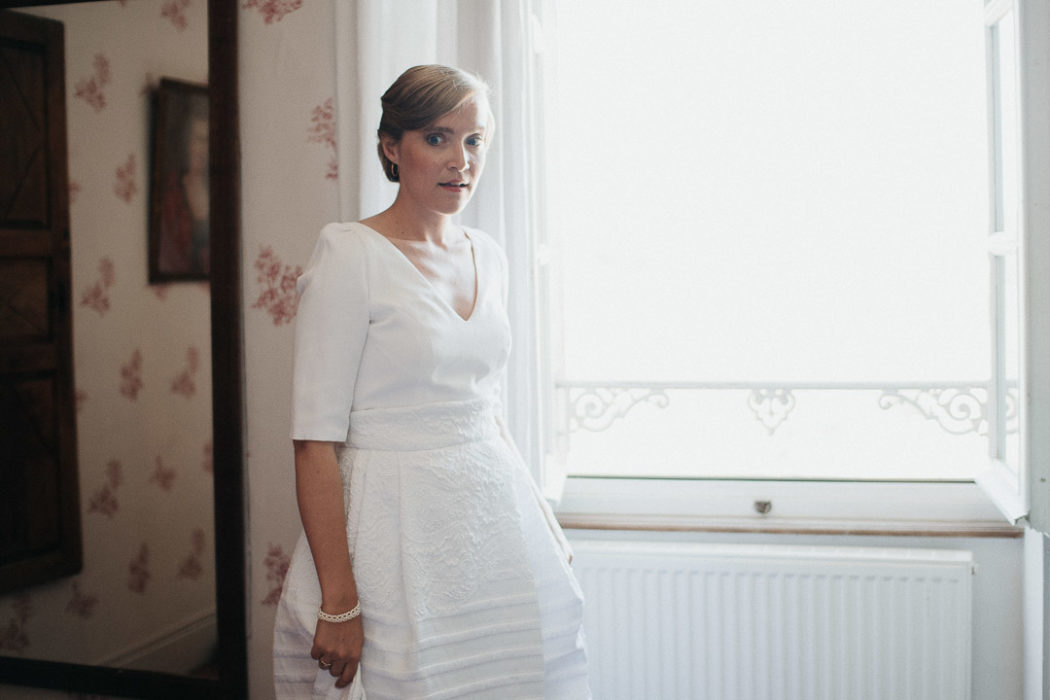 beautiful bride standing at the window soft light