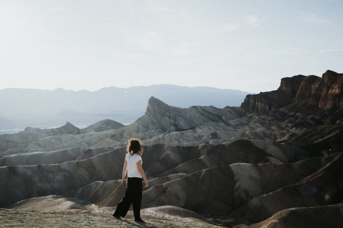 Girl standing before Zabriskie Point in Death Valley National Park watching the sunset