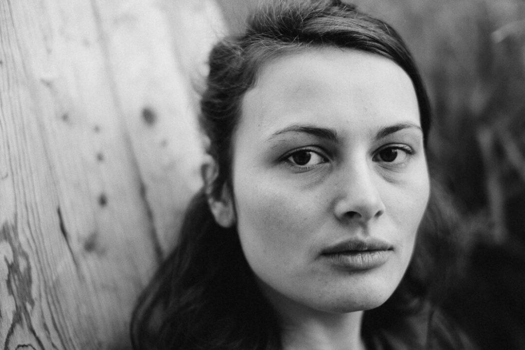 portrait en noir et blanc Manon Gilbert assise dans une chaise en bois