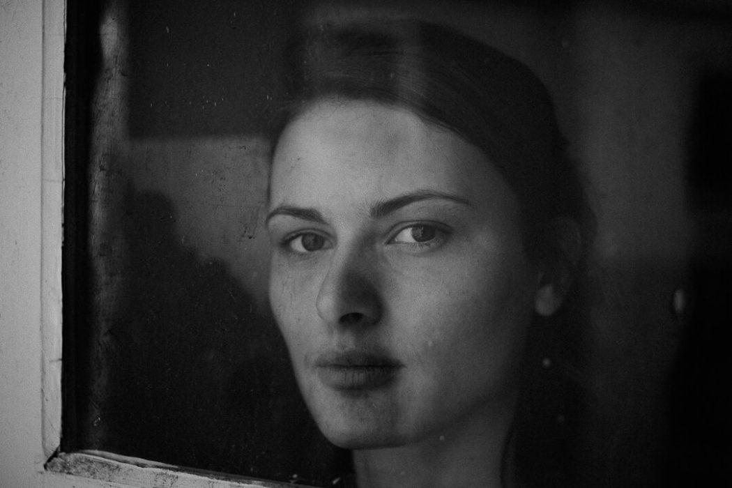 portrait en noir et blanc derrière une fenêtre de Manon Gilbert